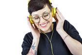 Happy young woman listening music in headphones — Stock Photo
