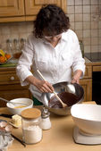 Mature woman makes the pastry in the kitchen — Stock Photo