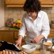 Mature woman makes the pastry in the kitchen — Stock Photo #43670909