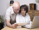 Two seniors play with a tablet computer — Stock Photo
