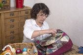 Mature woman by sewing and quilting — Photo