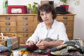 Mature woman by sewing and quilting — Stock Photo