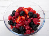 Glass bowl filled with red fruits — Stock Photo