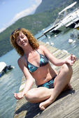Redhead young woman doing yoga on the waterside — Stock Photo