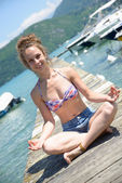 young woman doing yoga on the waterside — Стоковое фото