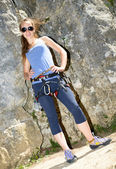 Young woman climbing a rock wall — Stock Photo