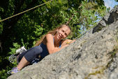 Young woman climbing a rock wall — Foto Stock