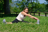 Sporty young woman makes stretching exercises — Stock Photo