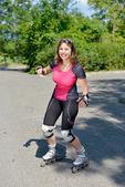 Bela jovem fazendo rollerskate em uma faixa — Foto Stock