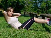 Sporty young woman makes stretching exercises — Stockfoto