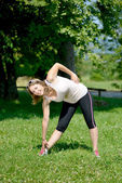 Sporty young woman makes stretching exercises — Stock fotografie