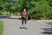 Ganska ung kvinna gör rullskridsko på ett spår — Stockfoto