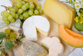 Assortment of french cheeses and seasonal fruit — Stock Photo