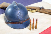 French helmet of the First World War with a gun on french flag — Stock Photo