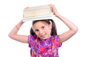 Schoolgirl with pile of books on head — Stock Photo