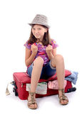Girl sitting on a suitcase — Stock Photo