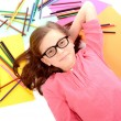 School girl lying on the floor with color pencils — Stock Photo #50512551