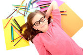 School girl lying on the floor with color pencils — 图库照片