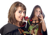 Two young women in disguise halloween with a glass of blood and  — Стоковое фото