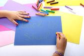 En tjej skriver tillbaka till skolan på blått papper — Stockfoto