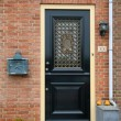 Black front door with openwork metal iron gate on a red brick wall — Stock Photo