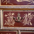 Old metal keyhole crown on an old chest of drawers painted with gold floral ornament — Stock Photo