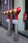 001 Shiny metal red water plug with seals and plugs on the street, Красный блестящий металлический пожарный кран  с пломбами и затычками на улице — Stock Photo