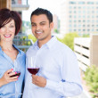 Portrait of man and woman toasting wine on outside balcony — Stock Photo #29524871