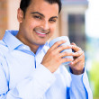 Handsome guy enjoying his drink on a balcony — Stock Photo