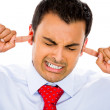 Closeup portrait of young businessman with fingers keeping his ears shut — Stock Photo