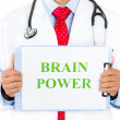 Closeup portrait of a health professional holding up a sign that says brain power — Stock Photo