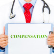 Closeup portrait of health care professional with stethoscope and red tie holding a sign that says compensation — Stock Photo #29612409