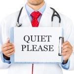 Closeup retrato de la salud profesional con corbata roja y un estetoscopio sosteniendo un letrero que dice silencio por favor — Foto de Stock