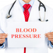 Closeup portrait of serious, confident health care professional with red tie and stethoscope holding up sign which says blood pressure — Stock Photo