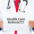 Foto Stock: Closeup portrait of health care professional with red tie and stethoscope holding up sign which says Health Care Reform