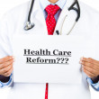 Closeup portrait of health care professional with red tie and stethoscope holding up a sign which says Health Care Reform — Stock Photo #29612613