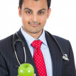 Closeup portrait of a confident health care professional or doctor or nurse in a business suit, offering you an apple — Stockfoto