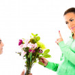 Young man standing on one knee and giving a bunch of flowers to his girlfriend — Stock Photo #29615827