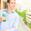 Closeup portrait of handsome guy drinking his beverage on outside balcony — Stock Photo