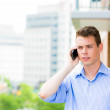Portrait of man having   conversation on cell phone outside on balcony — Stock Photo