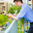 Portrait of handsome guy using his cell phone, texting, web, while relaxing on outside balcony — Stock Photo