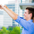 Portrait of happy, handsome, successful guy raising hands, arms outstretched in celebration and success, enjoying life on outside balcony — Stock Photo
