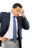 A frustrated young businessman holding his head while — Stock Photo