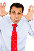 Man sticking his tongue out with thumbs in his ears — Stock Photo