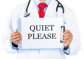 Closeup portrait of health care professional with red tie and stethoscope holding up sign which says quiet please — Stock Photo