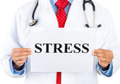 Closeup portrait of serious health care professional with a red tie and stethoscope holding a sign which says stress — Stock Photo