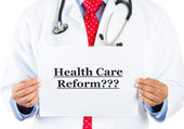 Closeup retrato do profissional com a gravata vermelha e estetoscópio segurando uma placa que diz a reforma dos cuidados de saúde de saúde — Foto Stock