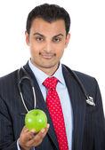 Närbild porträtt av en säker hälso-och sjukvårdspersonal eller läkare eller sjuksköterska i kostym, erbjuder dig ett äpple — Stockfoto