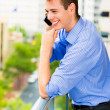 Portrait of handsome, happy man talking on his cell phone while on his outside balcony — Stock Photo