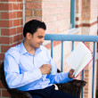 Young, handsome man reading book and enjoying drink on balcony — Stock Photo